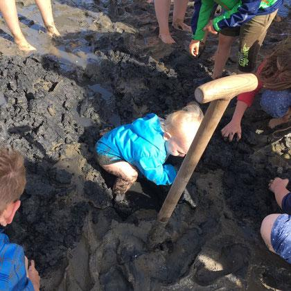 Wattwandern - Ein kleines Kind in einer blauen Jacke spielt in einem Loch, das im Schlick im Wattenmeer mit einer Schaufel gegraben wurde