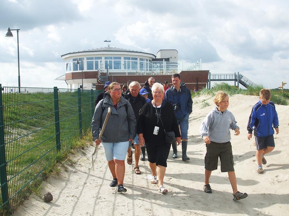 Wattführerin Martina Rieken läuft mit einer Gruppe in Richtung Wattenmeer, für eine familienfreundliche Wattwanderung in Nessmersiel