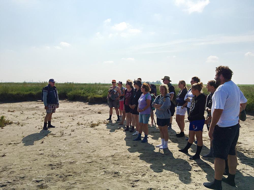 Wattführer Martin Rieken erklärt den Teilnehmern vor der Wattwanderung alles wichtige und beantwortet Fragen, sie stehen am Strand vor grünen Wiesen