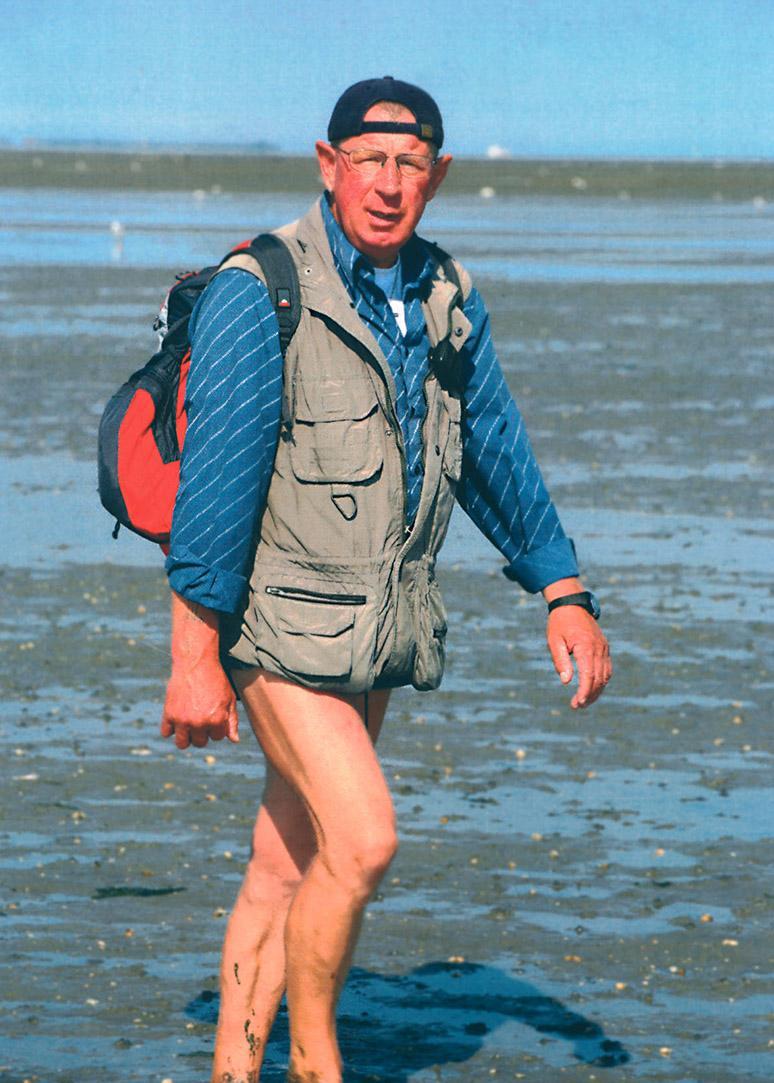 Staatlich geprüfter Wattführer Martin Rieken läuft im ostfriesischen Wattenmeer. Er trägt eine kurze Hose, ein Hemd, eine Weste sowie eine Cappy und einen roten Rucksack.