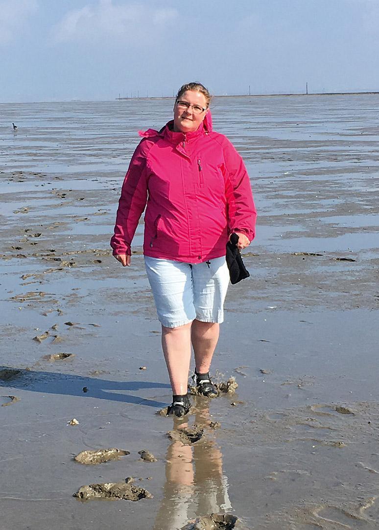 Staatlich geprüfte Wattführerin Martina Rieken läuft im Wattenmeer, sie trägt eine kurze Jeans sowie eine pinke Jacke und lächelt in die Kamera.