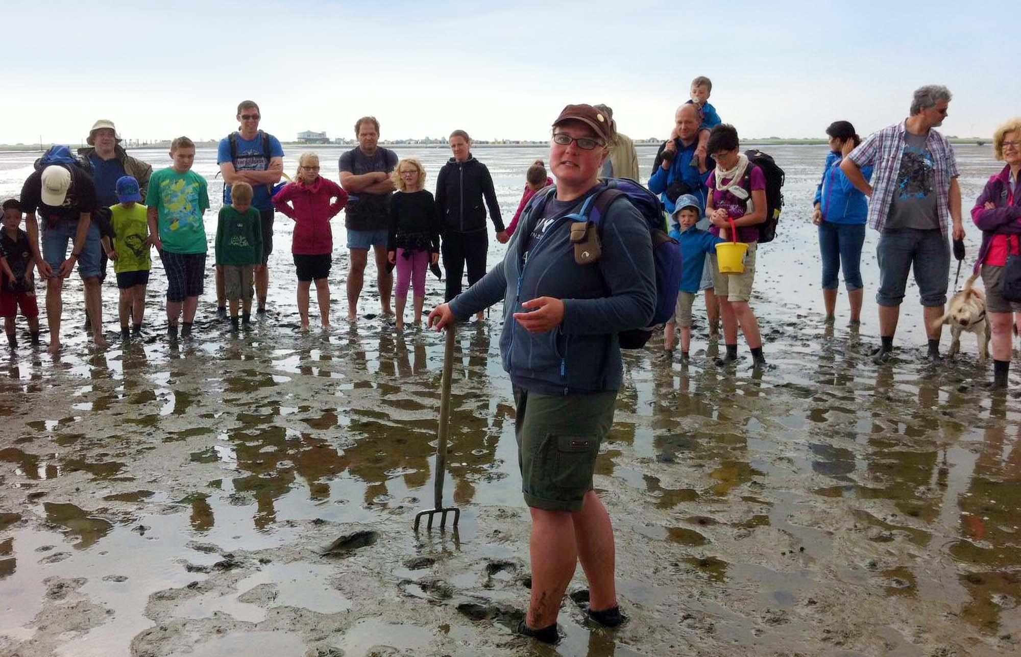 Wattführerin Martina Rieken erklärt in Nessmersiel neugierigen Teilnehmern einer Familienwattwanderung Dinge über das Wattenmeer